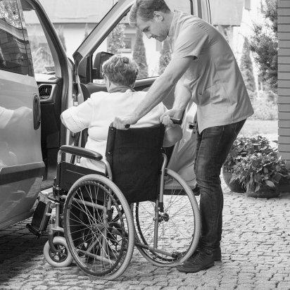 caretaker helping elder lady in wheelchair