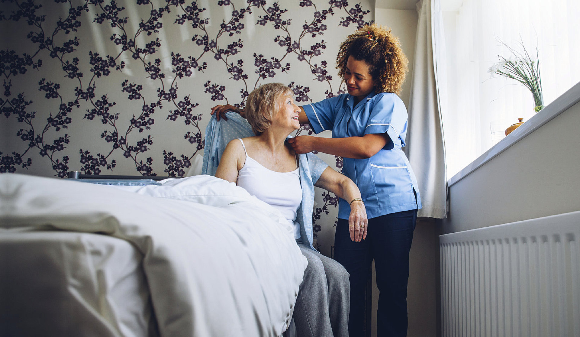 caretaker helps elder lady dress up
