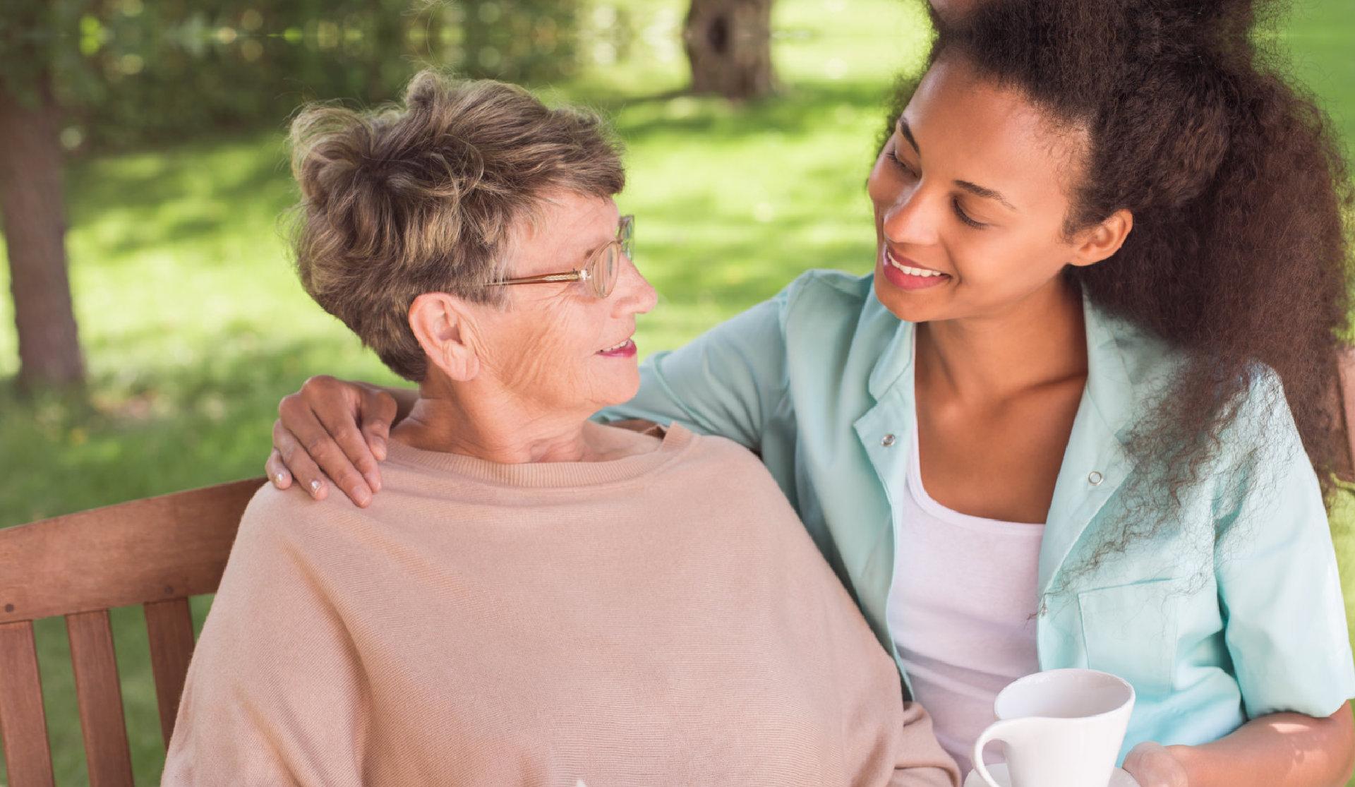 caretaker sits beside elder lady