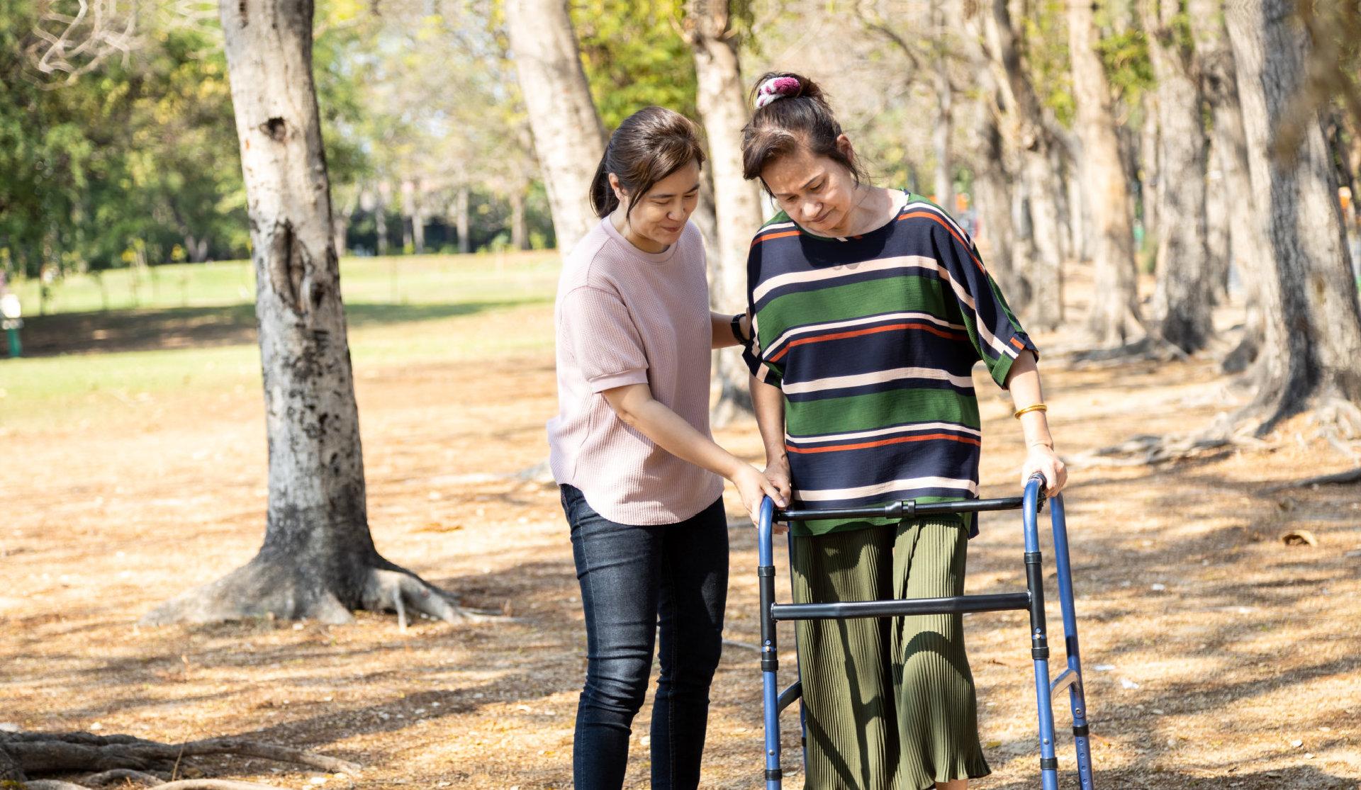 woman helps elder lady in walker